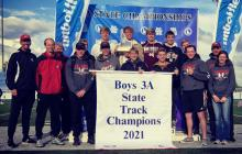 The Kimberly boys track team poses with its state championship trophy and banner at Middleton High School on Saturday, May 22. | Photo via Kimberly School District